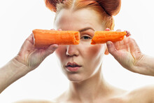 A Close-up Portrait Of A Red-haired Girl With Clear Skin And A Carrot In Her Hands. Isolated On A White Background.