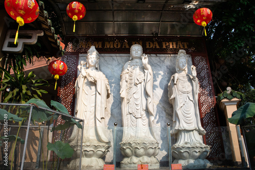 Three white stone statues of buddhist deities at the entrance of a temple Canvas Print