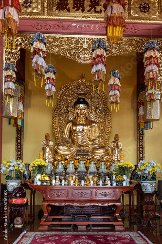 Golden sitting Buddha on an altar, inside a temple Canvas Print