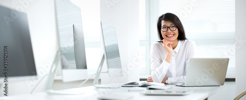 Fototapeta Asian business woman smiling at camera in an office obraz