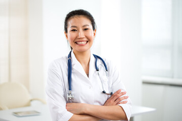 Portrait of smiling asian female doctor in a gray background for your text.