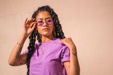 Urban Session. Young Dark-skinned Woman With Long Braids Wearing Purple Glasses On A Plain Background, Looking To The Right