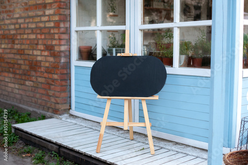 Photo Empty Wooden easel on street