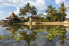 Buddhist Monastery Nga Phe Kyaung Surrounded By Vegetation, Reflected On The Waters Of Inle Lake, Myanmar, Burma, Southeast Asia. Symmetrical Picture. Tropical Vegetation. Palm Trees