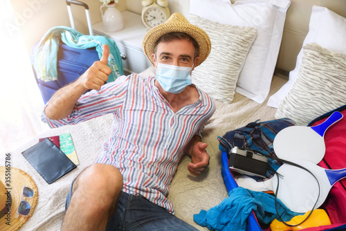 Foto Man on vacation in room protected with mask ok gesture