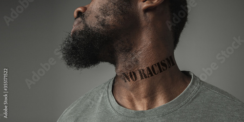Valokuvatapetti Close up portrait of a black man tired of racial discrimination has tattooed slogan no racism on his neck