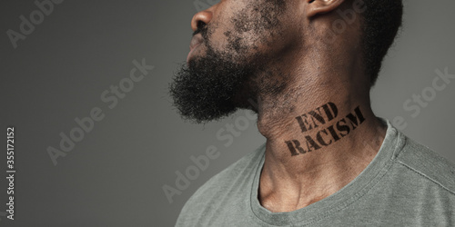 Close up black man tired of racial discrimination has tattooed slogan end racism on his neck Tapéta, Fotótapéta