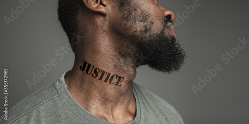 Photo Close up portrait black man tired of racial discrimination has tattooed slogan justice on his neck