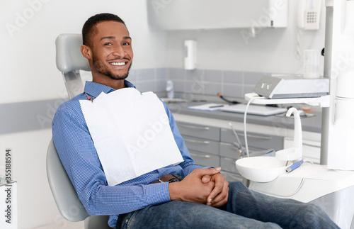 Happy black guy sitting on dentist chair, attending dental clinic Fototapeta