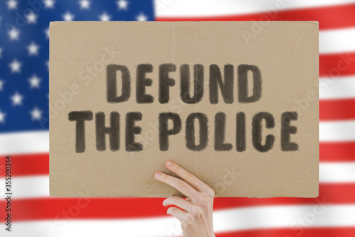 Fototapeta The phrase  Defund the police  on a banner in men's hand with blurred American flag on the background