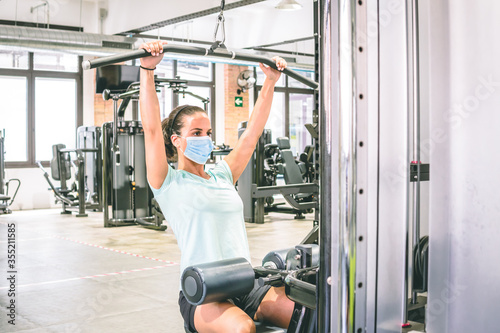 Fotografía young woman does strength training in a gym with her mask on.