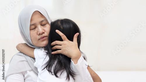 Fotografia Asian muslim mother hijab calming her sad and crying daughter, single mom and ba