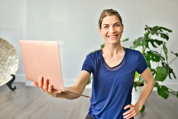 Nice yoga teacher woman holding computer in a studio class indoors