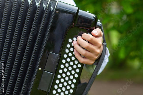 Obraz na plátne Play the accordion. Close-up, outside on the lawn