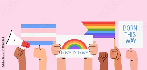 People hold signs, banner and placards with lgbt rainbow and transgender flag during pride month celebration against violence, descrimination, human rights violation Fototapeta
