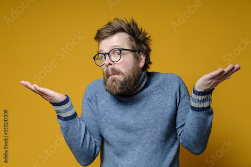 Fotografiet Strange man with an innocent and embarrassed expression on his face shrugs and spreads arms to the sides, on a yellow background