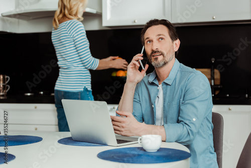Fototapety, obrazy: Selective focus of man talking on smartphone near laptop and cup of coffee in kitchen
