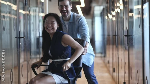 Fotografía Happy overjoyed business people have fun ride on chair in office hall, asian fem