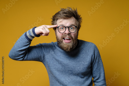 Irritated shaggy man with glasses holds a finger near his temple, showing interlocutor that he is an idiot Canvas Print