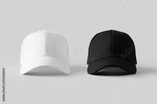 White and black baseball caps mockup on a grey background, front view Fototapete