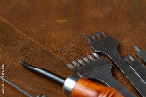 Fotografija The tools of the Leather craftsman are placed on the leather