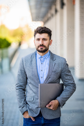 Handsome young businessman holding his laptop w standing on the street Fototapeta