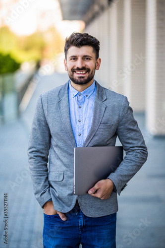 фотографія Handsome young businessman holding his laptop w standing on the street