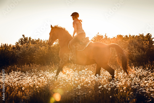 Obraz Frau galoppiert im Sonnenuntergang durch Blumen - fototapety do salonu