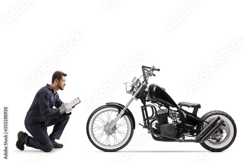 Motorbike mechanic in a uniform kneeling and looking at a chopper and writing a Fotobehang
