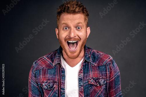 Valokuvatapetti Close-up shot of amazed and joyful adult redhead male model with beard smiling b