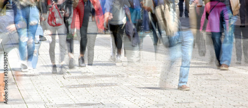 Fototapeta Crowd of abstract people walking in the shopping pedestrian zone, multiple exposure and motion blur, panoramic format, copy space obraz