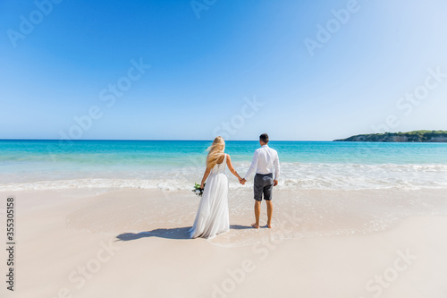 Foto Newlyweds holding hands hugging at white sandy tropical caribbean beach landscap