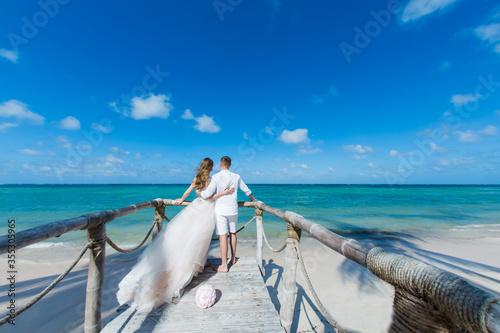 Carta da parati Newlyweds holding hands hugging at white sandy tropical caribbean beach landscap
