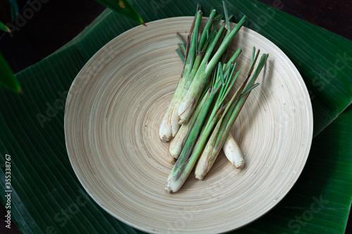Fototapeta Fresh Lemongrass (Cymbopogon citratus) or citronella, serai on a wooden plate. obraz