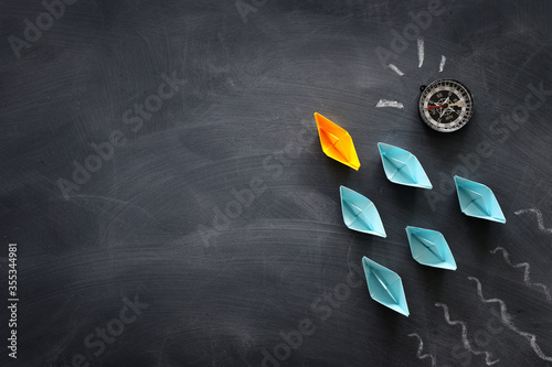 Fotografía Leadership banner concept with paper boat on blackboard background