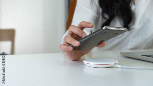 Working Woman putting smartphone on wireless charger in office Fototapete