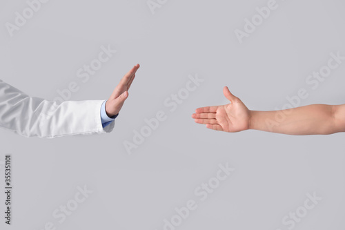 Doctor refusing to shake hand of patient on light background Tapéta, Fotótapéta