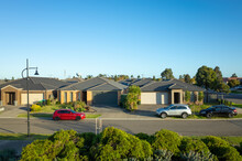 Elevated View Of Modern Suburban Homes In An Australian Suburb With Family Cars Parked On Side Of The Street.
