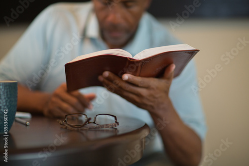 African American man praying and reading the Bible. Fototapeta