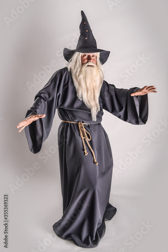Tablou Canvas A stern grey-haired bearded wizard in a gray cassock and a cap is practicing sorcery and doing magic against a light background