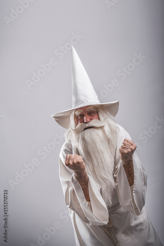 Fotografie, Obraz A grey-haired severe wizard in a white cassock is doing sorcery and magic against a light background