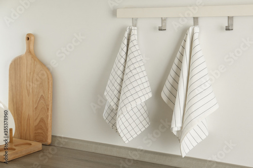 Obraz Different kitchen towels hanging on hook rack indoors - fototapety do salonu