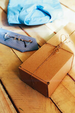 Brown Squared Present Box With Jute Rope, Blue Shirt And Tie On A Wooden Background. Fathers Day Concept