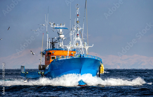 Canvas-taulu Fishing boat returns after fishing to its port