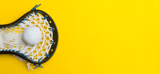Lacrosse ball and stick on yellow background. Team sport concept