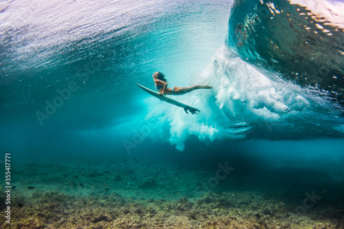 Fotomural woman in bikini doing duck dive with the surfboard under the waves