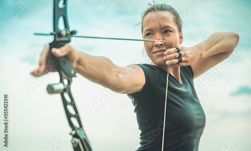 Fotografering archery, young woman with an arrow in a bow focused on hitting a target