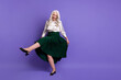 Full length photo of attractive aged white haired lady good mood hold long green skirt dancing pensioner retro party raise leg wear white blouse isolated pastel purple color background