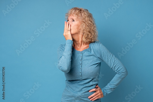 Fotografie, Obraz Scared middle aged senior woman covering mouth with hands feel horrified, stunned old blond female received shocking news