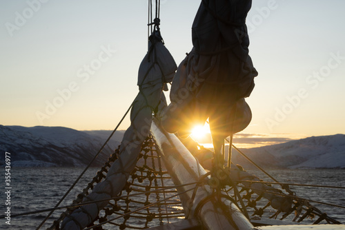 Sunrise in a Norwegian fjord called Kaldfjord with a sailing mast and sail in the foreground Fototapete